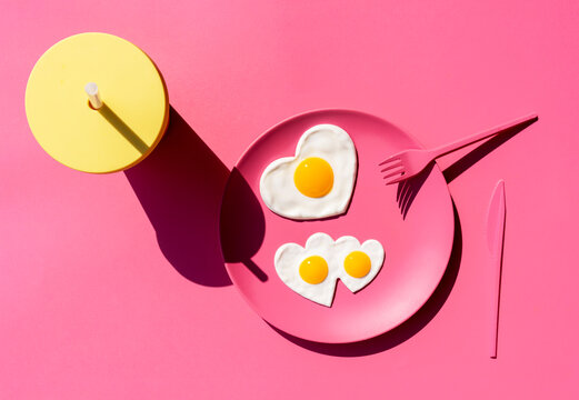 Disposable cup and plate of heart shaped fried eggs