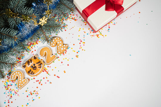 New Year 2022 background with gift and gingerbread . Holiday mood card. Top view, copy space. Family traditions, DIY, celebration concept. Festive background with homemade gingerbread cookies.