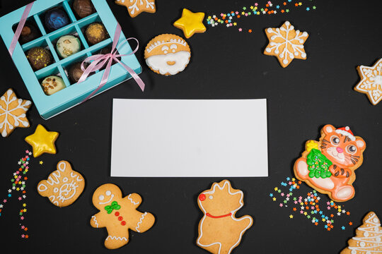 Christmas background with gingerbread on gray surface. Holiday mood card. Top view, copy space. Family traditions, DIY, celebration concept. Festive background with homemade gingerbread cookies.