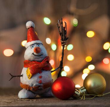 Christmas snowman decoration against the backdrop illumination and fir tree