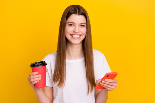 Photo of young happy positive woman smile hold phone takeout coffee smile isolated on shine yellow color background