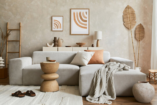 Elegnat living room interior design with mock up poster frame, grey corner sofa, coffee table and personal accessories. Pastel neutral colours. Template.