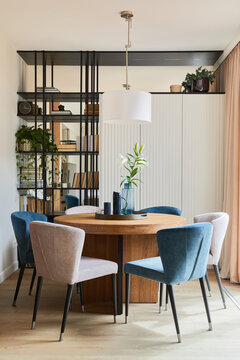 Stylish elegant dining room interior design composition with velvet armchairs, design rouded wooden table and beautiful personal accessories. Glamour interior design inspiration. Template..