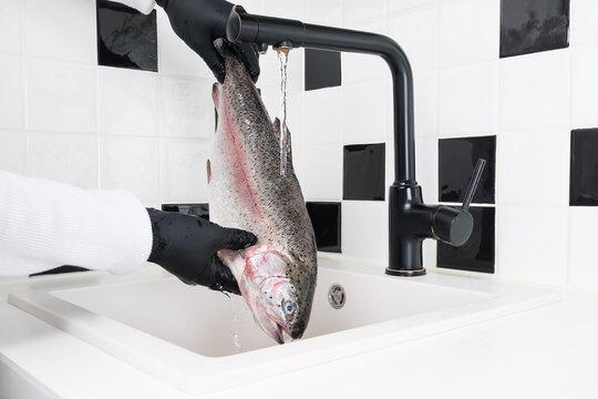 hands in black rubber gloves handle fish under running water