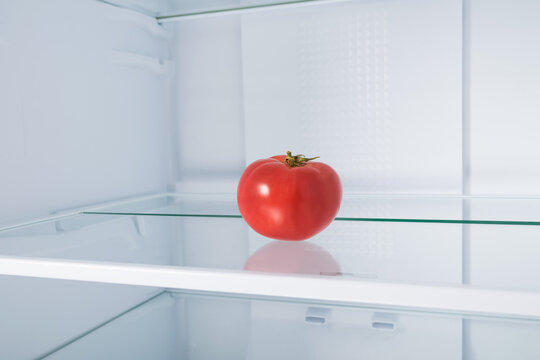 red tomato on a glass shelf in the refrigerator
