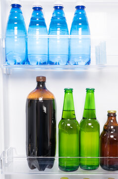 beer and bottled water stand on the shelves in the refrigerator door, front view
