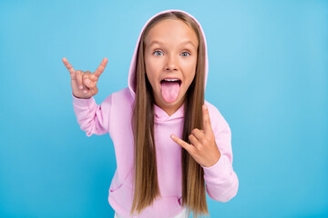 Fototapeta Photo of crazy excited blonde amazed positive young little girl fingers rock sign music lover isolated on blue color background obraz