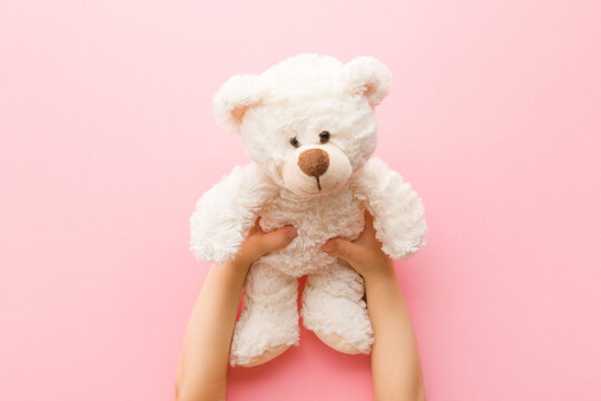Smiling white teddy bear in baby girl hands on light pink background. Pastel color. Closeup. Point of view shot. Kids best friend. Top down view.