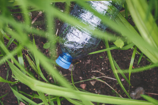 Used plastic waste, water bottle on the grass, pollution problem and recycling concept