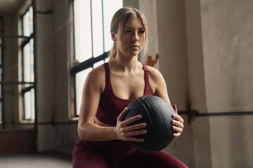 Obraz Determined sportswoman working out with medicine ball in gym - fototapety do salonu