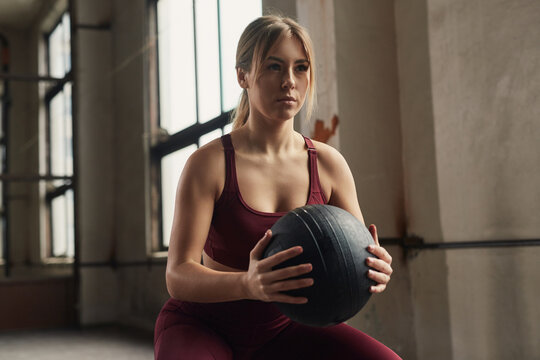 Determined sportswoman working out with medicine ball in gym