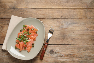 Fototapeta Delicious salmon carpaccio served on wooden table, flat lay. Space for text obraz