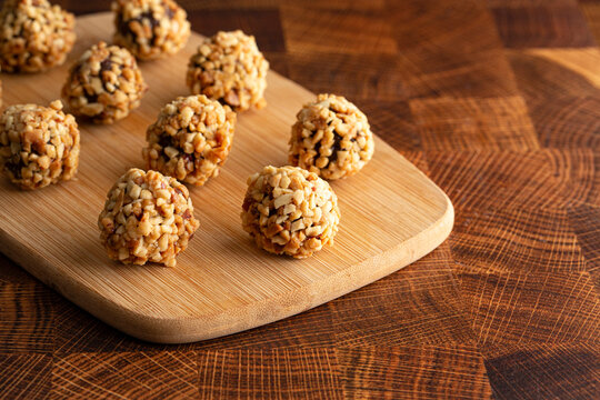 Group of Chocolate Peanut Butter Energy Balls on a Wooden Butcher Block