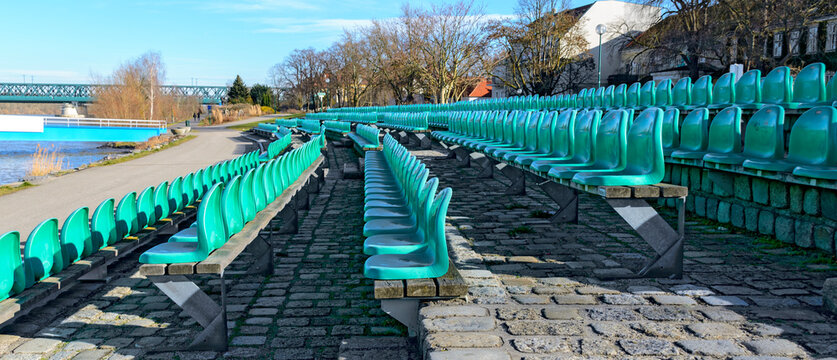 rows of green seats made of plastic for spectators at the landing aera at the open-air Danube stage of Tulln, Austria