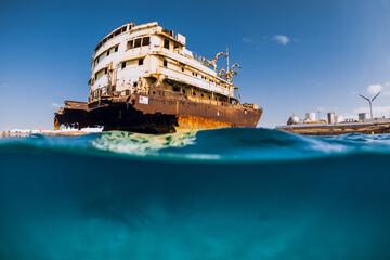 Split shot in blue ocean with wreck ship. Arrecife, Lanzarote