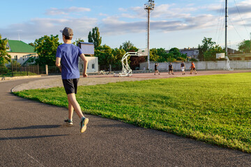 Obraz concept of sports and health - teen boy runs along the stadium track, a soccer field with green grass. - fototapety do salonu