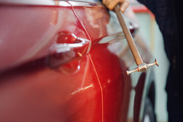 Obraz Master auto mechanic removal of dents defects without painting on car body on service station - fototapety do salonu