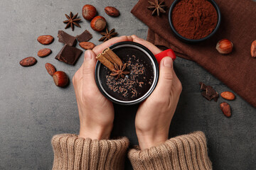Fototapeta Woman with mug of yummy hot chocolate at grey table, top view obraz