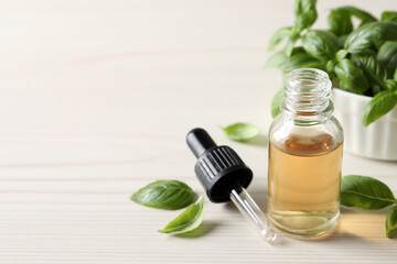 Fototapeta Glass bottle of basil essential oil and leaves on white wooden table. Space for text obraz