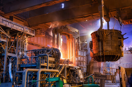 A metallurgical ladle filled with molten metal bucket is suspended on a special crane beam