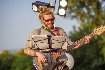 Handsome bearded man playing guitar at outdoor concert