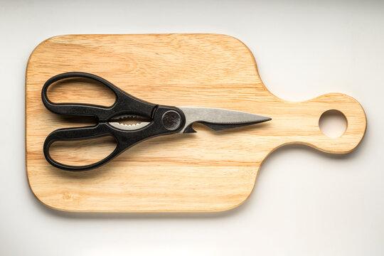 Black kitchen shears on a wooden cutting board