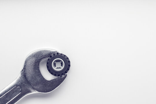 A wrench tries to turn a wheel from a toy car. Tire fitting concept