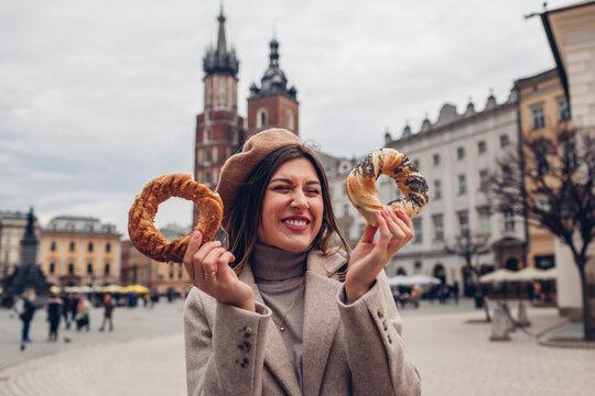 Woman eating bagel obwarzanek traditional polish cuisine snack on Market square in Krakow. Travel Europe in autumn