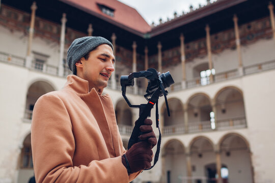 Man shooting footage using steadicam stabilizer with camera filming Wawel castle in Krakow Poland. Travel Europe