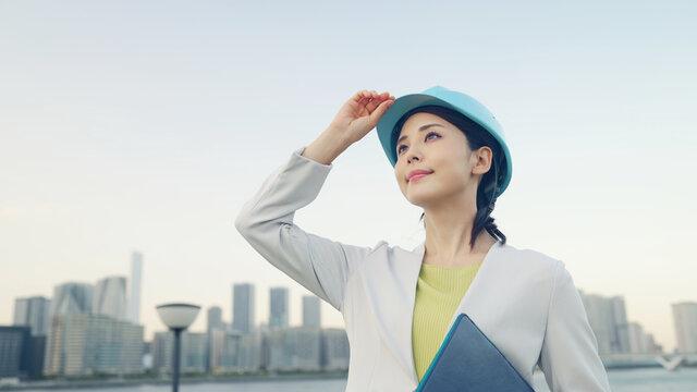 ヘルメットをかぶって都市を眺める女性 設計士 建築家