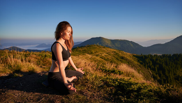 Attractive young woman in sportswear sitting on grassy hill in lotus position and doing Gyan mudra hand gesture while mediating outdoors. Sporty woman doing meditation yoga exercise in mountains.