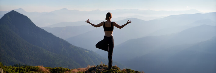Obraz Back view of young woman performing yoga pose on grassy hill and looking at beautiful mountains. Sporty woman standing on one leg and doing Gyan mudra hand gesture while practicing yoga outdoors. - fototapety do salonu
