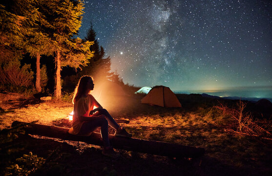 Side view of silhouette of woman relaxing near forest in campsite. Female sitting near bonfire and admiring starry sky. Concept of adventure and night camping in the mountains.