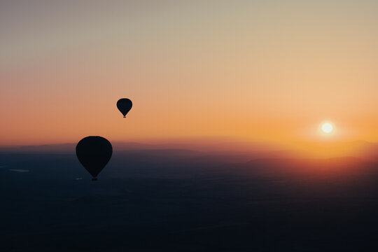 hot air balloon silhouette with sun rising over the mountains