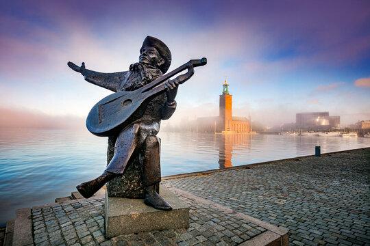 STOCKHOLM, SWEDEN - JUN 21, 2015: Evert Taube monument on background of Stockholm City Hall
