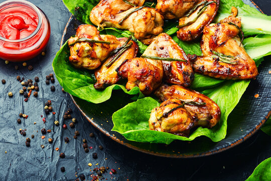 Grilled chicken wings on lettuce leaves