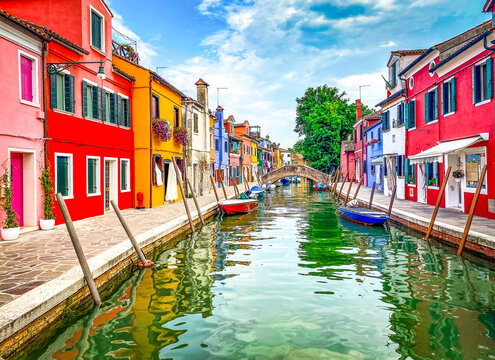 Boats and colorful traditional painted houses in a canal street houses of Burano island, Venice, Italy