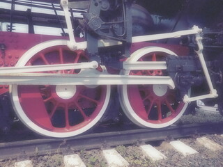 Retro vintage wheels of a locomotive or train close up. Red large heavy metal wheels with piston guiding mechanisms. Locomotive of the 19th - 20th centuries with a steam engine. Blurred soft focus