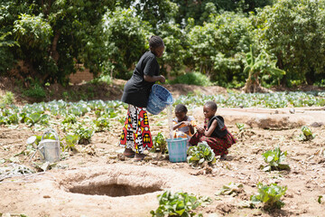 Obraz Group of black African girls at the village water hole filling water buckets; drought concept - fototapety do salonu