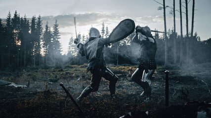 Fototapeta Dark Age Battlefield: Two Armored Medieval Knights Fighting with Swords. Battle of Armed Warrior Soldiers, Killing Enemy in Mysterious Forest. Cinematic Smoke, Mist, Light in Historic Reenactment obraz