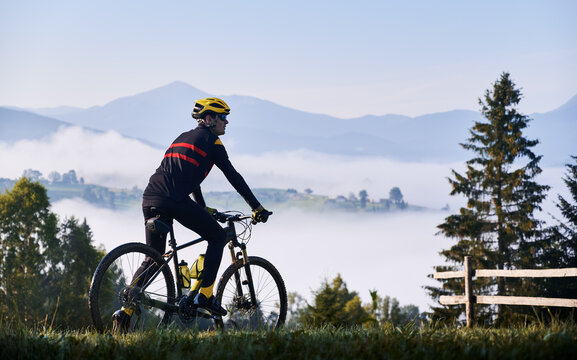 Silhouette of man cyclist in cycling suit riding bike on grassy hill. Male bicyclist enjoying the view of majestic mountains during bicycle ride. Concept of sport, bicycling and nature.