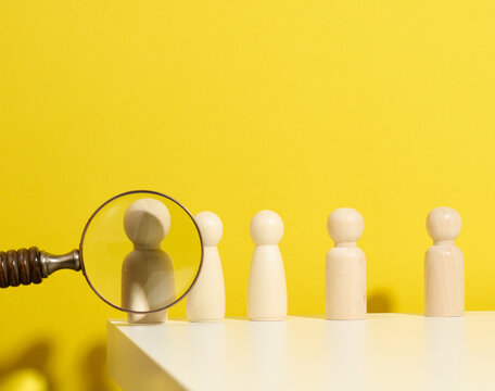 figurines of men on a white table and magnifying glass. Concept of searching for employees in the company, recruiting personnel, identifying talented and strong personaliti