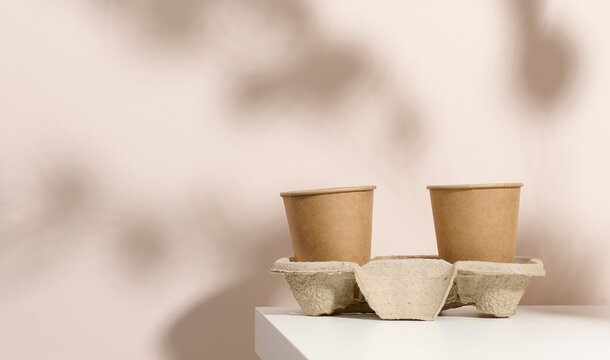 paper cardboard brown cups for coffee and tea, beige background. Eco-friendly tableware, zero waste