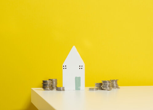 miniature wooden house and a stack of coins on a white table. Real estate purchase, mortgage concept. Rise in real estate prices, subsidies from the state