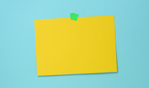 blank rectangular yellow sheet of paper glued on a blue background. Place for an inscription, announcement