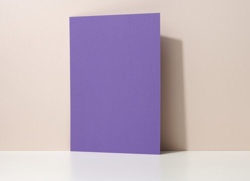 blank purple cardboard sheet of paper with shadow on white table. Template for flyer, announcement