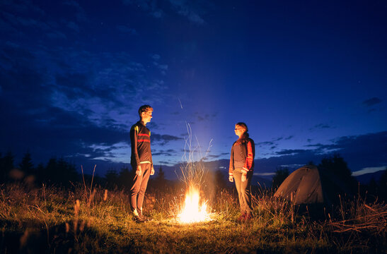 Horizontal snapshot of couple of tourists spending time together in camping. Young boy and girl near campfire in the evening outdoors in nature. Standing looking at fire in summer night