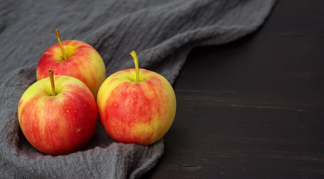 Red apple on a black wooden table.