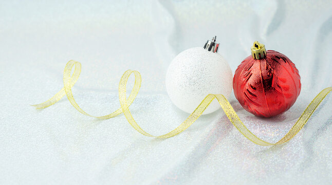 Red and white Christmas ball on a white glitter background.