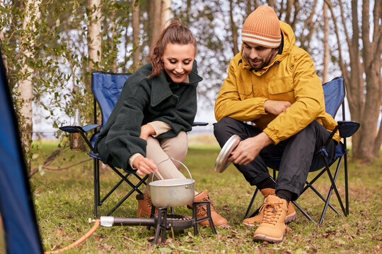 camping, tourism and travel concept - happy couple cooking food in pot on tourist gas burner at tent camp